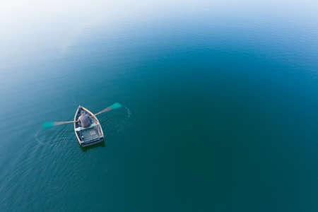 Fisherman in a wooden boat paddles, top view. Soft focus.