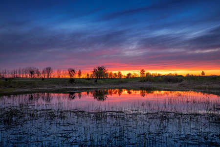 Dramatic bright dawn or sunset over the lake. Bright summer landscape.