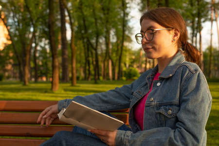 Girl in the park on a bench reading a book