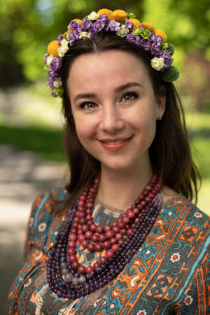 Brunette in a wreath and necklace, happy young woman.