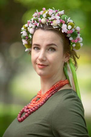 Attractive brunette in a green dress with a blue wreath and a pink necklace, portrait. Imagens
