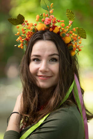 Attractive girl in a green dress, wreath and necklace.