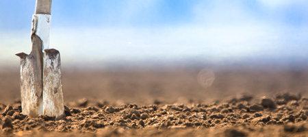 Shovel in fresh soil on a plowed field.