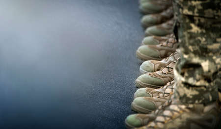 The soldiers' legs are dressed in ankle boots and camouflage pants. Close-up, selective focus. Фото со стока
