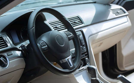 Modern car interior. The driver's seat is decorated with white and black leather and metal. Modern electronic devices on the car panel.