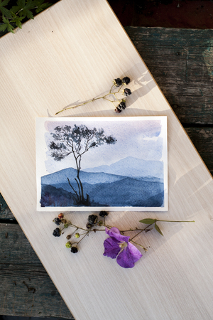 watercolor sketch depicting the mountain landscape photographed on a light background, lies next to a branch of blackberry and clematis flower.