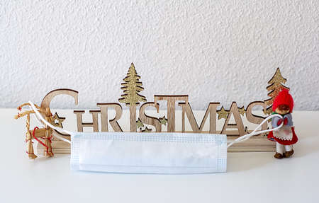 Wooden letters forming Christmas and dolls holding a medical mask in a wrinckled and white background