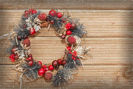 green door: Christmas wreath with decorations on the wooden background.