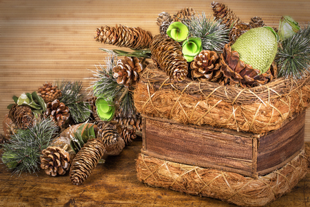 cristmas card: Christmas decorative composition with basket and pine cones on wooden background. Stock Photo