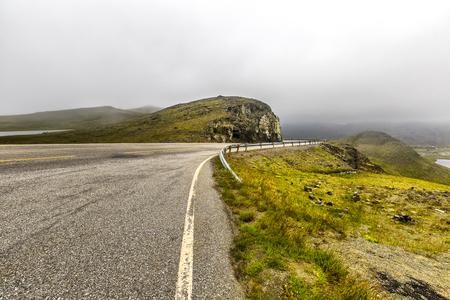 Beautiful road goes through norwegian mountains in heavy fog in Troms country, Norway. Reklamní fotografie