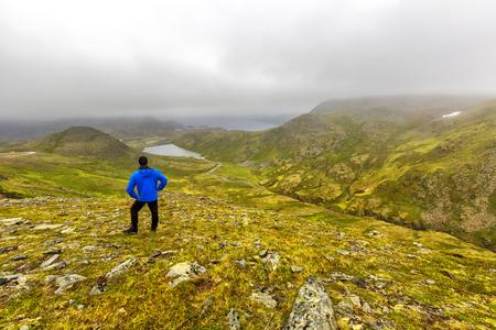 Young man standing on Kvanangen mountain, watching at Skorpa uninhabited island in Troms country, Norway. Reklamní fotografie