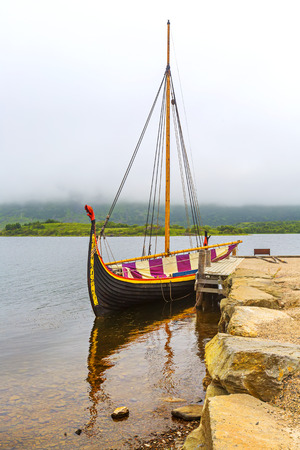 Old Viking ship on a lake on cloudy day in Lofoten Islands. Norway.