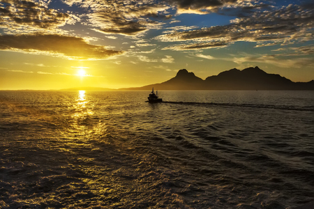 Magical view of the traveler to the sea:  sun at sunset,  mountains, fjord and ship. Norway Reklamní fotografie
