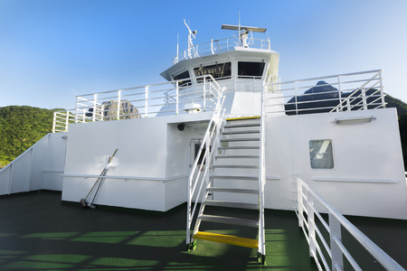 Close up of white cruise liner or ferry ship and blue sky on sunny day.