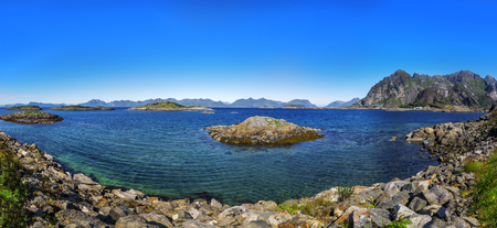 Scenic view of the waterfront harbor in Henningsvaer in summer. Henningsvaer is a fishing village and tourist town located on Austvagoya in the Lofoten Islands. Norway.