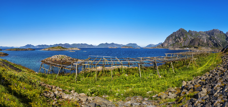 Scenic view of the waterfront harbor and Racks for air-dried fish in Henningsvaer in summer. Henningsvaer is a fishing village and tourist town located on Austvagoya in the Lofoten Islands. Norway.