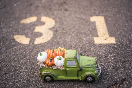 Green harvest truck full of Colorful fall pumpkins with blurred background. Thanksgiving wallpaper Stock Photo