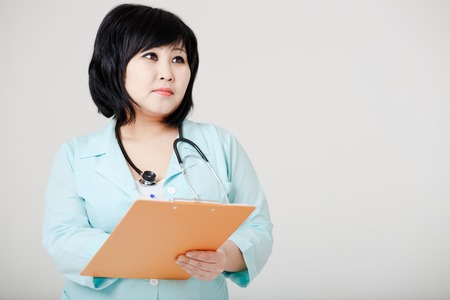 diagnose: Young female Asian doctor with stethoscope standing still, thinking and writing diagnose.
