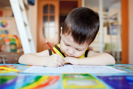 artist: Busy little boy drawing with felt pens at home with colorful interior, three years old.