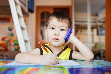 three years old: Surprised little boy talking on smartphone at home while drawing with felt pens, three years old.