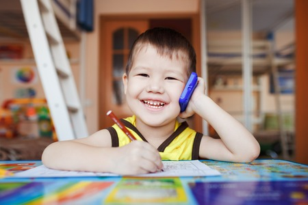 three years old: Happy little boy talking on smartphone at home while writing letters, three years old.