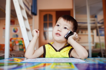 important phone call: Little boy takes an important call on his cell phone, while drawing at home with felt pens. He portrays a businessman. Stock Photo