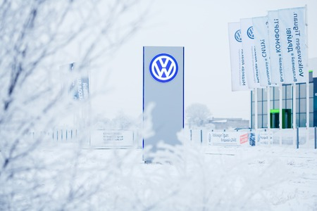 scandal: ABAKAN, RUSSIA - JANUARY 3, 2016. Volkswagen dealership logo stand through snow-covered trees on a frosty winter day. Volkswagen emissions scandal.