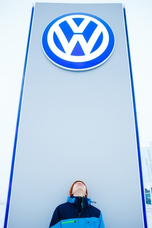 straight up: ABAKAN, RUSSIA - JANUARY 3, 2016. Man standing at bottom of a Volkswagen dealership logo stand, looking straight up on the sign. German automotive manufacturing company emissions scandal. Editorial