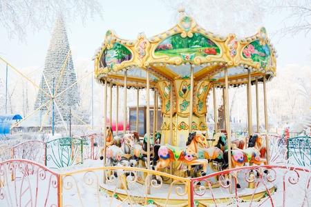 Merry-go-round con los caballos tradicionales cubiertas de nieve. Detrás del carrusel (rotonda) gran árbol de Navidad. Parque de la ciudad durante el día de invierno frío.