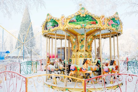 Merry-go-round with traditional horses covered with snow. Behind the carousel (roundabout) big Christmas tree. City park during the winter frosty day.