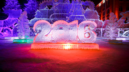 ice alphabet: Happy new year 2016 written with ice letters, sculptures in the park with beautiful illumination at night. Ice alphabet, numbers. Stock Photo