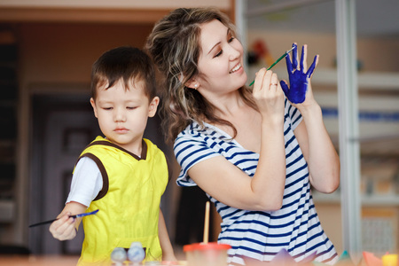 children painting: Merry childhood, a little boy playing with his mother, draws, paints on the palms. Teaching children drawing, development of creative abilities. Painting of a palm. Natural daylight.