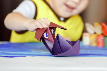 vessel sink: Paper battle, an origami figure Godzilla attacks a paper boat, childrens games. The development of imagination and creative thinking, creating origami art paper toys. Violet paper ship.