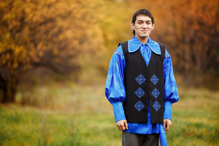 fulfilled: Cheerful, handsome man dressed in traditional national costume of blue with black jacket decorated with ornamentsl. Blurred background of an autumn forest with gold foliage and vibrant yellow colors.