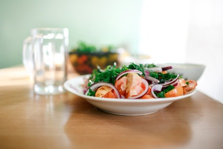 healthy economy: Minimalistic fresh mixed vegetable salad of tomatoes, onions and parsley. Empty glass mug in the background. Healthy food, vitamins in harsh living conditions, simple food, economy. Natural light, selective focus. Healthy breakfast, weight loss concept. Stock Photo