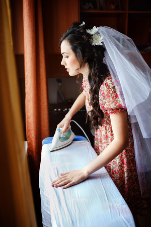 iron curtains: The bride preparing for the wedding ceremony, modern iron ironing her wedding dress on the ironing board, by the window with brown curtains, natural light. Motley house dress with a veil of bride. Stock Photo