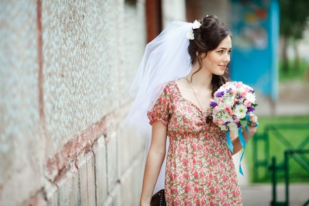 bride dress: The bride in a simple retro dress with a floral pattern, already wearing a veil and wedding bouquet and handbag in the hands, posing outside the house, looking to the side.