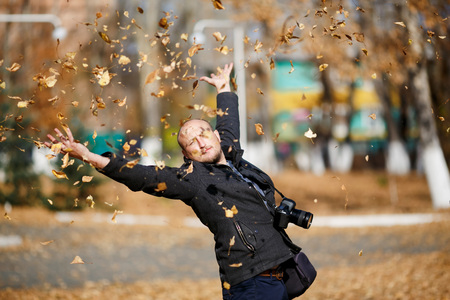 tons: Portrait of a happy male photographer with professional digital camera on his neck, he throws tons of leaves falling in the air in autumn park, enjoying the sunshine weather, glad and satisfied. Stock Photo