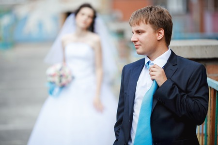The groom dark blue suit straightens turquoise tie with a sour face, in the background tired and frustrated bride waiting. The concept of long wait before the wedding, indecision, important decisions.