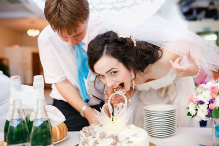 leaned: Impatient beautiful bride in a white dress leaned forward quickly and wants to try the wedding cake, groom in a turquoise tie stands nearby. Celebration, cake cutting. Wedding banquet at a restaurant.