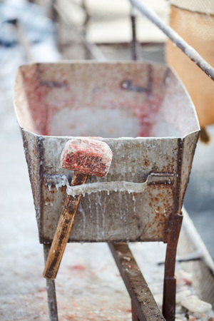 cruelty: Frostscale hammer to stun the trout fish with an ice crust hanging on a metal trolley. Trout farming in the winter, breeding fish for sale to restaurants. The concept of cruelty, harsh truth. Stock Photo