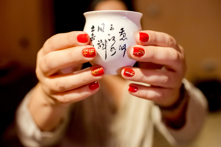 attributes: Manicure with Chinese characters close-up, Happy New Year. Attributes of the Chinese New Year, Spring Festival. In the hands of a real tea cup with the characters, offer a cup of tea.