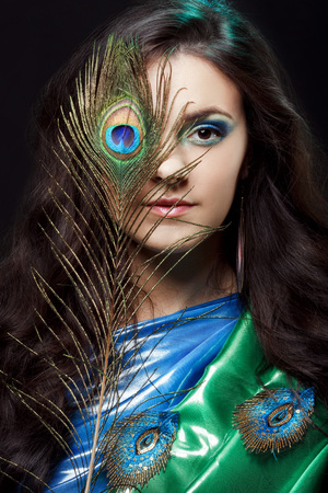 intrigue: Beauty portrait of beautiful girl covering the eyes of a peacock feather. Creative makeup peacock feathers. Attractive mysterious interesting lady. Perfect holiday expressive artistic makeup peacock feathers. Bright colors, harmonious green black yellow b