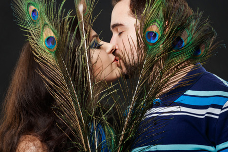 fantasize: Mysterious stranger girl with long eyelashes passionately kisses a regular guy hiding behind peacock feathers. Attractive young woman in a luxurious sheen, shiny fabric. Imagination, dream, fantasize.