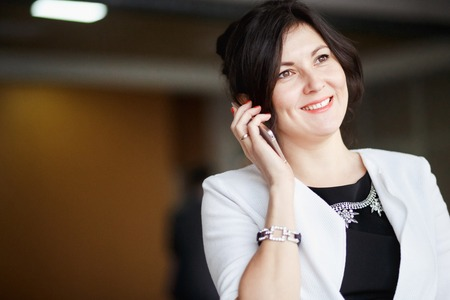 beaming: Attractive business woman talking on the phone, beaming smile, positive image, dressed in a white suit with a strict black dress. Negotiations, communications in the company, copy space for your text. Stock Photo