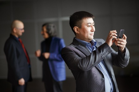 Businessman holding mobile smart phone using app texting sms message, preparing video call, wearing jacket, checking emails. Against background of men crowd discuss program of conference, indoors.