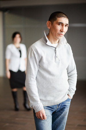 waits: A man in casual clothes with short hair thoughtfully looking directly into the camera, the employee gets a job. In the background, HR Director woman in a white suit and strict black dress waits. Stock Photo