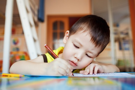 writing paper: The boy carefully and intently draws in a special notebook for drawing, education at home, pre-school training, the development of creative abilities of children. Classroom in the house. Stock Photo