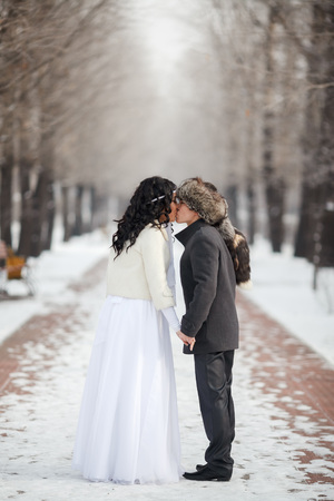 asian bride: Asian bride and groom kissing in the middle of snowy winter alley. Young man in winter coat and fur hat, bride in white wedding dress with sheepskin. Cold season warmed wedding dresses, wedding coat. Stock Photo