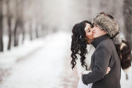 parejas romanticas: Ex�tica novia asi�tica y el novio bes�ndose en medio del callej�n de invierno cubierto de nieve. Hombre joven en abrigo de invierno y sombrero de piel, novia en vestido de novia blanco con piel de oveja. estaci�n fr�a ropa de abrigo. Copia espacio para el texto.